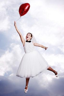 Braut hängt an einem Ballon vor Wolkenhintergrund Studiofoto Fotoparty JGA