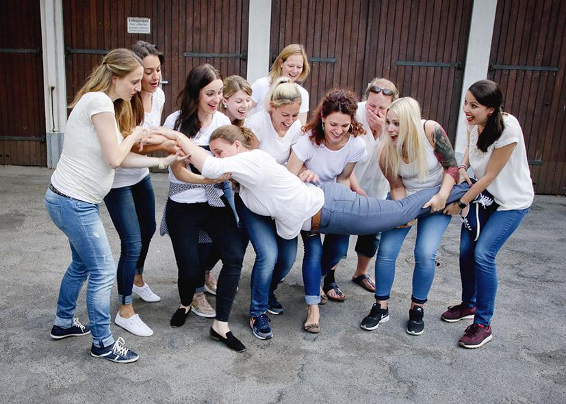 Eine Gruppe von Frauen versucht eien Frau hochzuheben Fotoparty