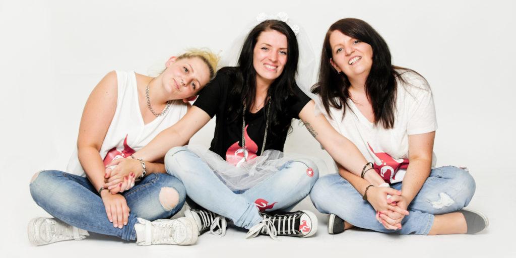 Fotoparty JGA Dortmund 2 Freundinnen und die Braut in Verkleidung im Schneidersitz auf weißem Hintergrund Idee Junggesellinnen Abschied Fotoshooting Dortmund