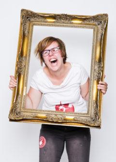 Fotoparty Mädel hält sich Rahmen vor Gesicht JGA
