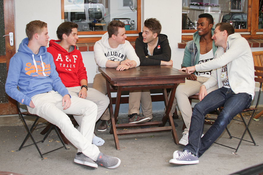 Gruppe Junggesellen und Beste Freunde sitzen an einem Tisch