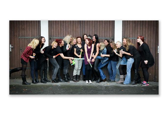 Viele junge Frauen stehen vor eine Holztor und lachen Fotoparty JGA Fotoshooting